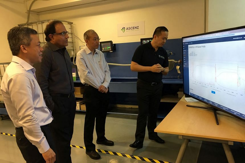 (From left) Mr Chia, Ascenz chief executive; Mr Iswaran, Trade and Industry Minister; Mr Sia, Ascenz chief technology officer; and Mr Bernard Siah, Ascenz product development manager, viewing a demonstration of Ascenz's proprietary monitoring system yeste