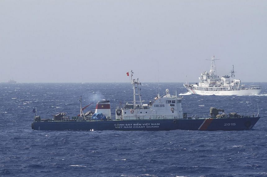 A ship (top) of the Chinese Coast Guard is seen near a ship of the Vietnam Marine Guard in the South China Sea, off shore of Vietnam in this May 14, 2014 file photo.
