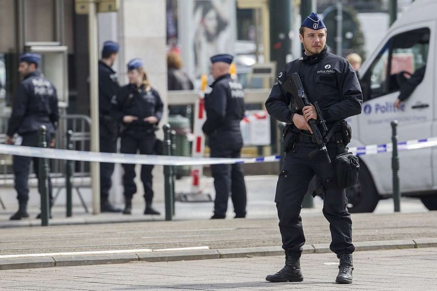 A Belgian police officer secures the zone outside a courthouse while Brussels attacks suspects Mohamed Abrini and Osama Krayem appear before a judge, in Brussels, Belgium, on April 14, 2016.