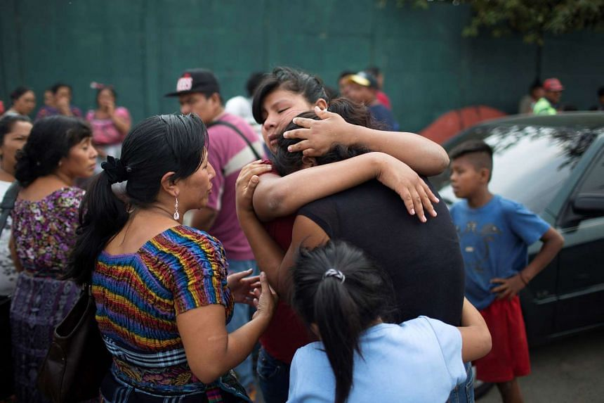Relatives of missing garbage collectors react as they wait for news of their loved ones outside a landfill dumpsite, where a massive pile of garbage collapsed and buried several people, in Guatemala City, Guatemala, on April 28, 2016.