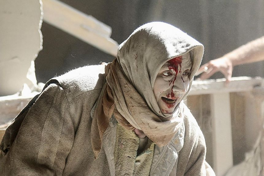 An injured woman at a site hit by air strikes in the rebel-held area of Old Aleppo in Syria on Thursday. More than 200 civilians have been killed in Aleppo over the past week in renewed violence that has shattered a partial truce in Syria's civil war