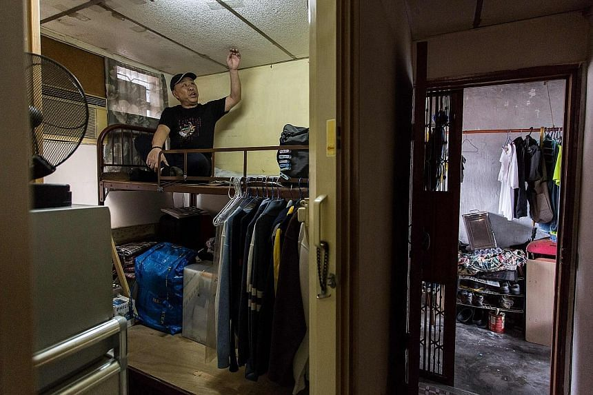 """A dweller of a cubicle flat, built within a subdivided """"rooftop house"""", which he shares with other tenants on the roof of a 10-storey building in Kowloon."""