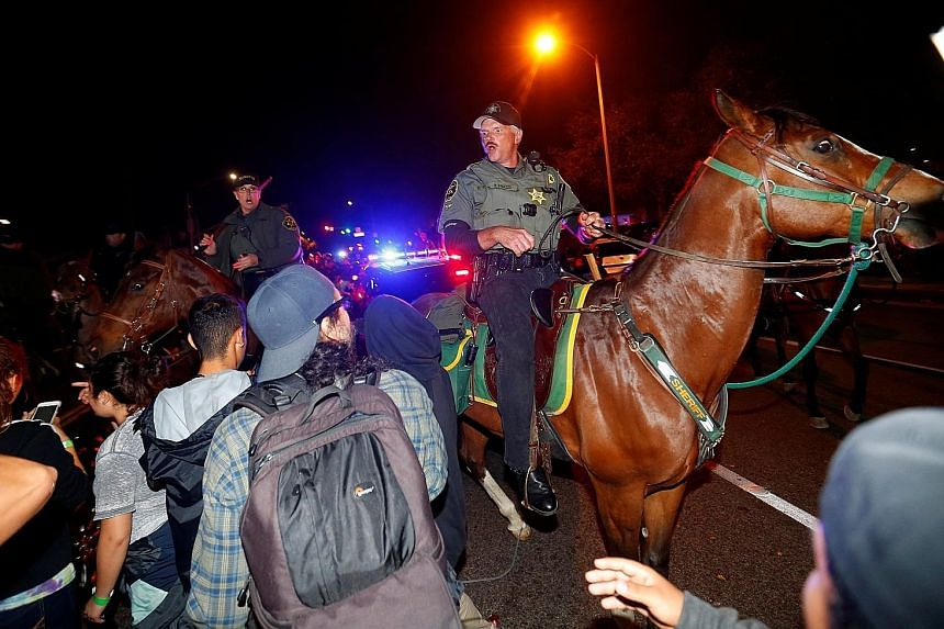 Sheriffs and police officers on horseback breaking up a group of demonstrators outside Republican presidential candidate Donald Trump's campaign rally in Costa Mesa, California, on Thursday. Observers see a Trump nomination as inevitable.