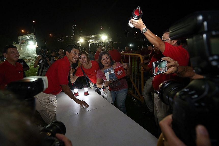 (Below) Dr Chee's supporters taking a picture with him last night at the field along Bukit Batok Industrial Park A, where he held his first rally of the campaign. In his speech, Dr Chee promised Bukit Batok residents that if he wins the by-election o