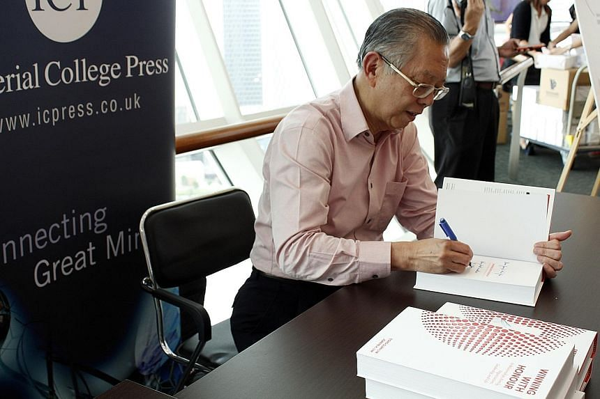 Mr Lim signing copies of his book - Winning With Honour In Relationships, Family, Organisations, Leadership, And Life - which is co-authored by his daughter Joanne.