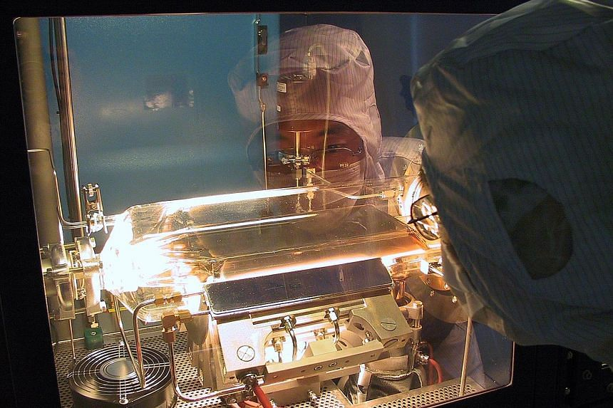 A DenseLight engineer processing wafers at its Changi Industrial Park facility. The firm's products are used in communications, healthcare, navigation, and oil and gas exploration and production.