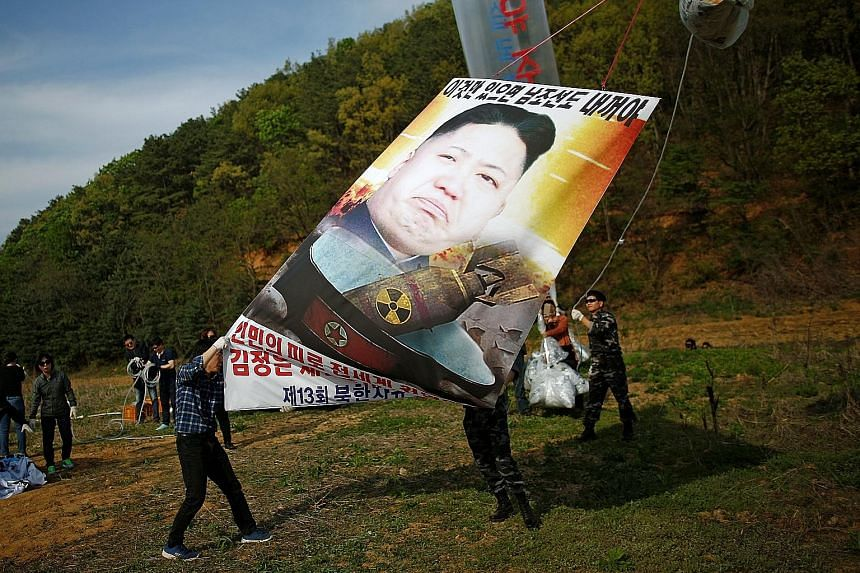 Activists near the demilitarised zone in Paju, South Korea, yesterday calling for the end of North Korean leader Kim Jong Un's reign. The secretive state is expected to conduct another nuclear test ahead of a party congress.