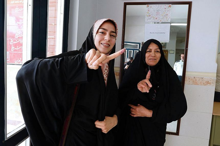 Iranian women displaying their ink-stained fingers after casting their votes yesterday in the second round of parliamentary elections at a polling station in Robat Karim, some 40km south-west of the capital Teheran. Polling stations opened at 8am loc
