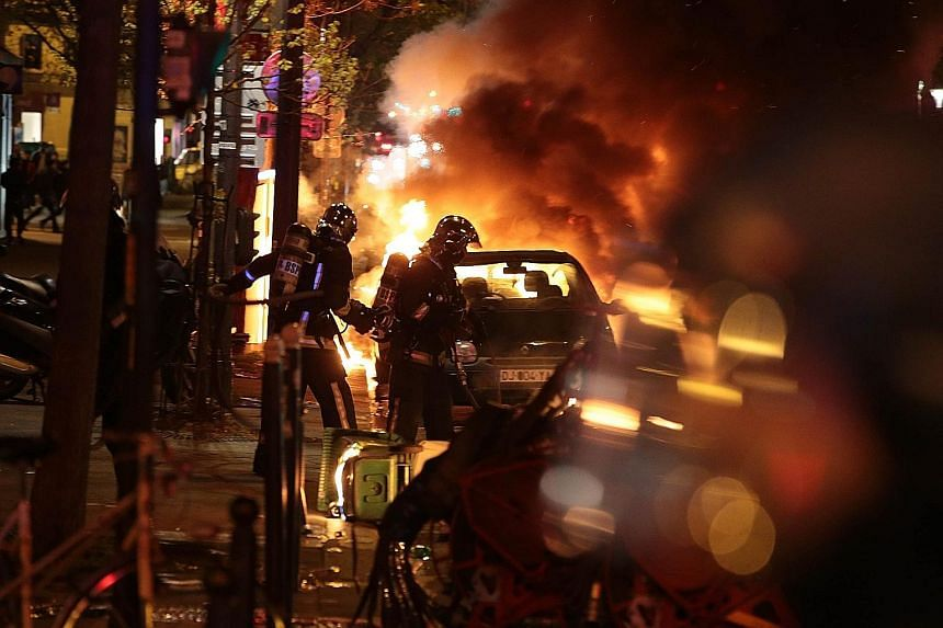 """Firefighters putting out the flames on a burning car early yesterday as French security officers cleared the Place de la Republique during a protest by the Nuit Debout, or """"Up All Night"""" movement."""