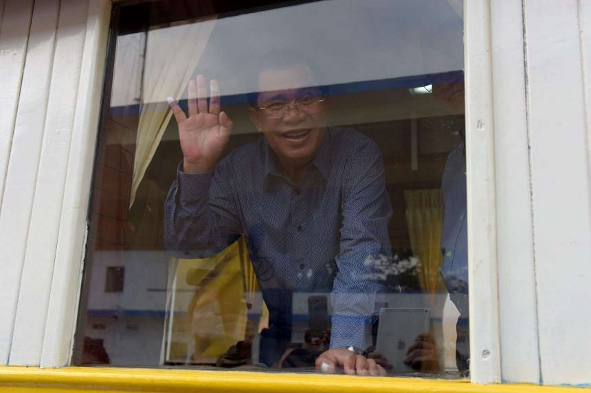 Cambodian Prime Minister Hun Sen waves from a train compartment window at the Phnom Penh train station on April 30, 2016, as the railway service resumes after years of suspension.
