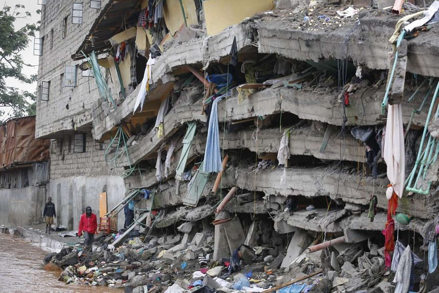 Local residents walk next to a collapsed building in the Huruma estate of Mathare slum, Nairobi, Kenya on May 1, 2016.
