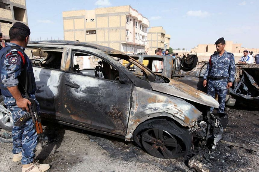 Policemen gather at the site of a car bomb attack in Samawa, south of Baghdad, May 1, 2016.