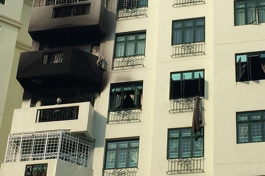 The smoke-blackened exterior of the condo unit at Hillview Green. One of the residents, Mr Timothy Ng, climbed down from the window of the seventh-floor unit to the floor below, after failing to open the main door. He went back up to open the door fr