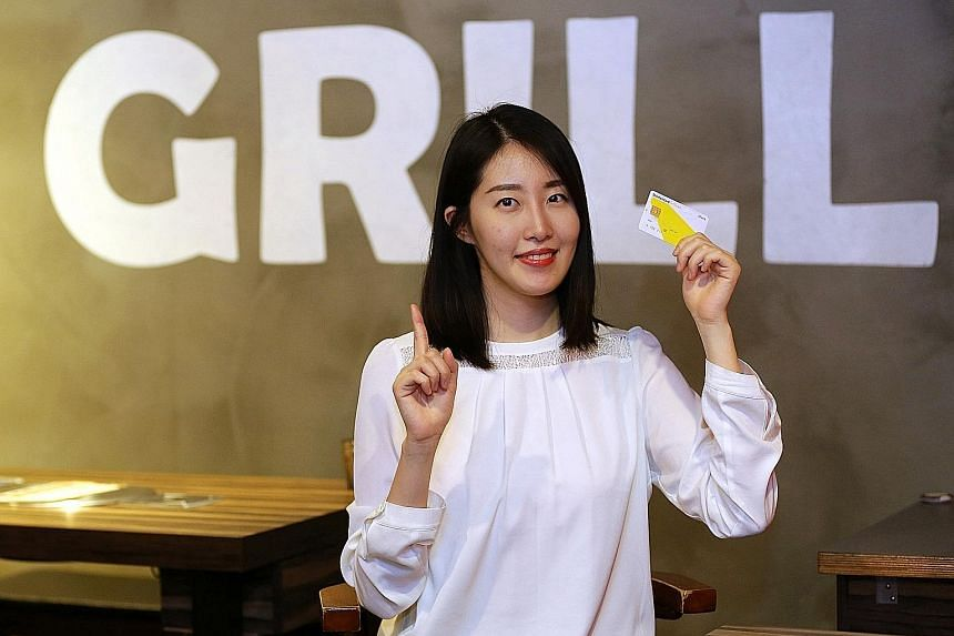 Ms Kim holding the debit card she uses for daily expenses. Only about 20 per cent of all payments in South Korea are made with cash, as credit cards, debit cards and T-money become more popular.