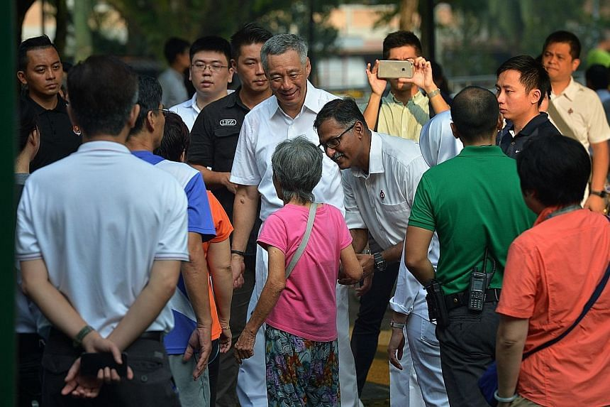 Mr Murali greeting an elderly resident at Bukit Batok Central Park yesterday as PM Lee looks on. Mr Lee said Mr Murali's commitment is beyond doubt, and he would be backed by a town council with a good track record.