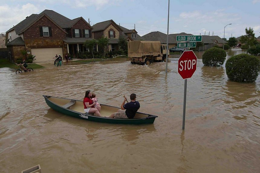 A woman holds a baby in a canoe as Texas Guardsmen arrive to assist after flooding in Brookshire, Texas, on April 20, 2016.