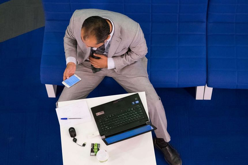 A trader using various devices to trade on the stock exchange. PHOTO: BLOOMBERG