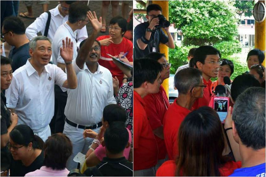 PM Lee and Mr Murali waving to residents at a block in Bukit Batok West Avenue 8 yesterday. The Prime Minister raised questions about the character of Dr Chee (right), seen here speaking to reporters yesterday in the constituency.