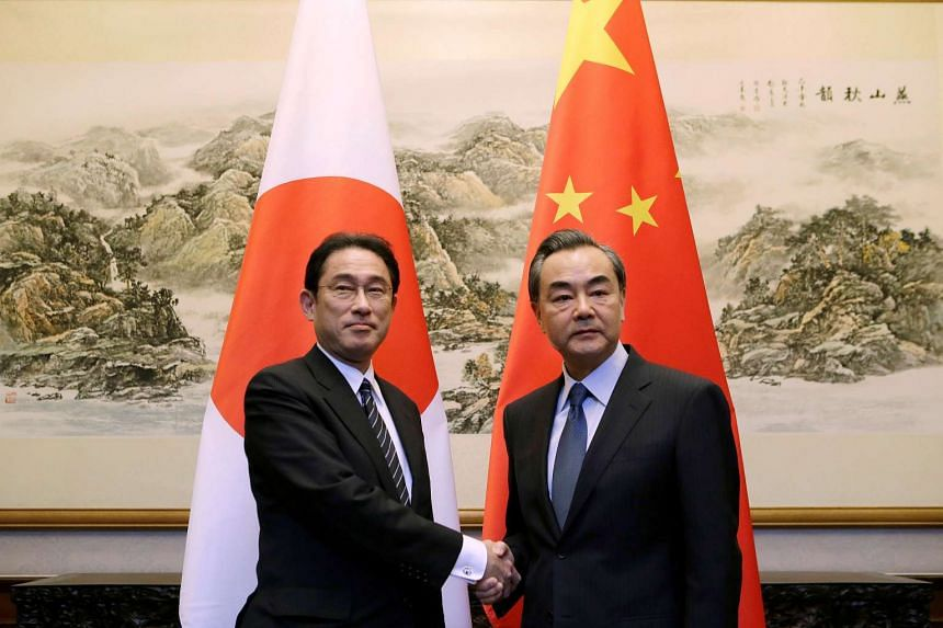 Japanese Foreign Minister Fumio Kishida (left) shakes hands with China's Foreign Minister Wang Yi in Beijing, China, on April 30, 2016.