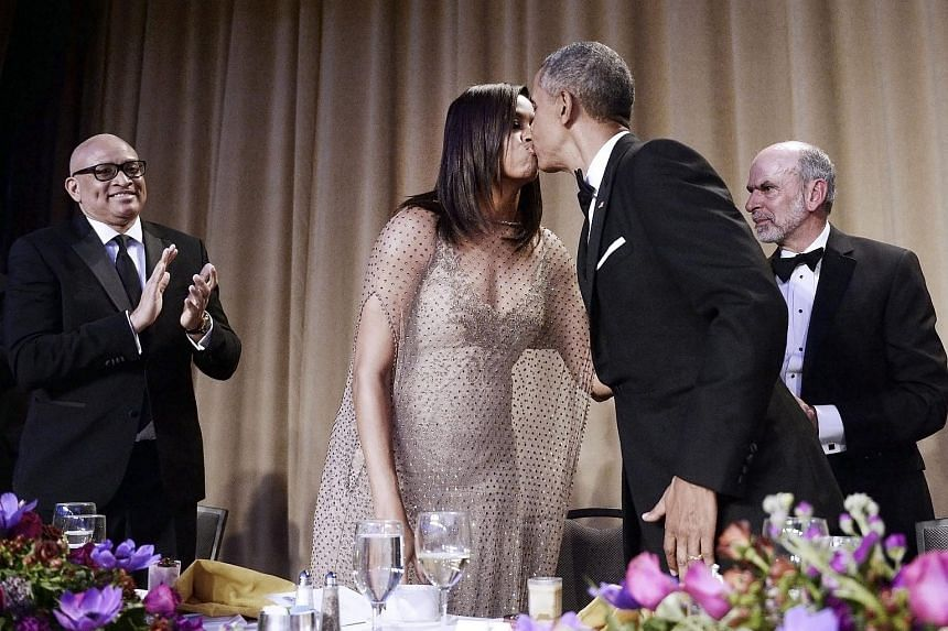 US President Barack Obama (second right) kisses First Lady Michelle Obama after delivering a speech as US comedian Larry Wilmore (left) applauds during the White House Correspondents' Association annual dinner.