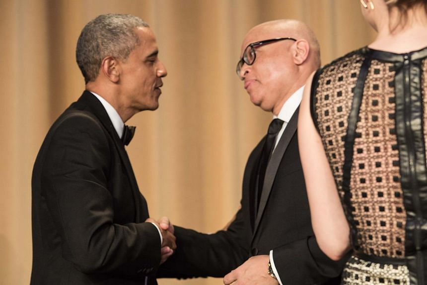 US President Barack Obama shakes hands with comedian Larry Willmore during the White House Correspondents' Association Dinner.