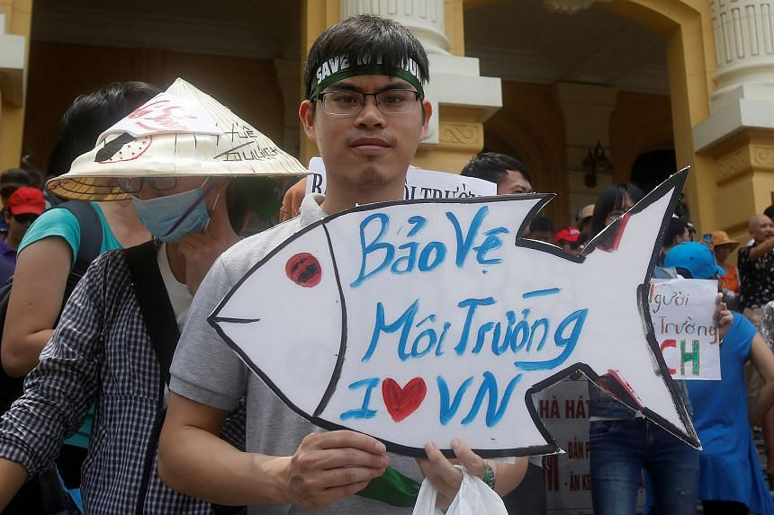 "A demonstrator holds a sign reading ""Protect the environment. I love Vietnam"" during a protest after the mass fish deaths, in Hanoi, Vietnam, on May 1, 2016."