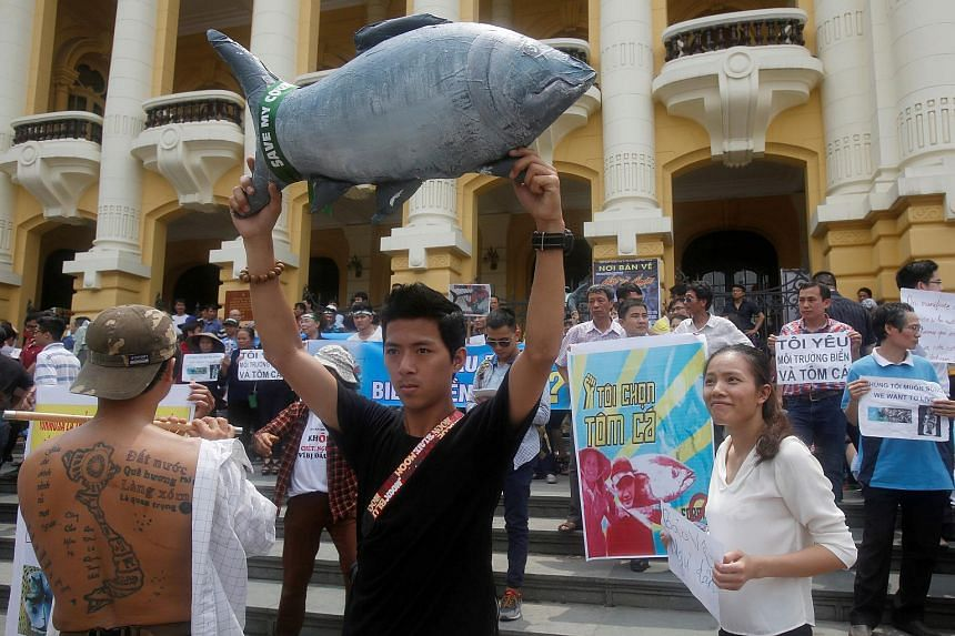Demonstrators hold up signs during a protest to demand cleaner waters in the central regions after the mass fish deaths in Hanoi, Vietnam, on May 1, 2016.