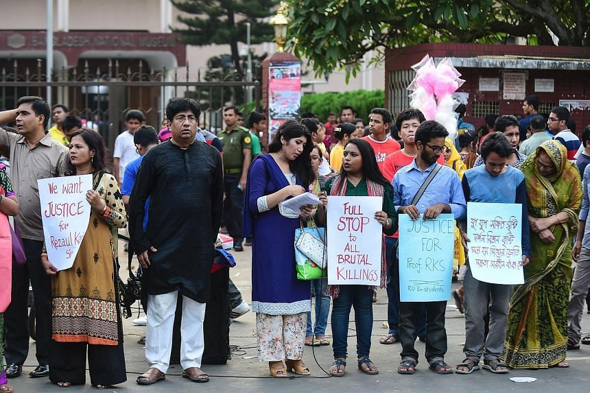 Protestors hold placards during a demonstration against the killing of a university professor in Dhaka, on April 29, 2016. There has been a spate of attacks against minorities, liberals and westerners in Bangladesh.