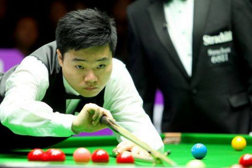 : Ding Junhui of China plays a shot on the snooker table.