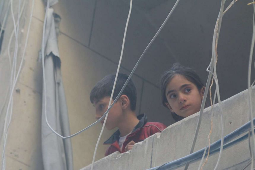 Children look out from a balcony at a site hit by airstrikes in a rebel-held area of Aleppo.