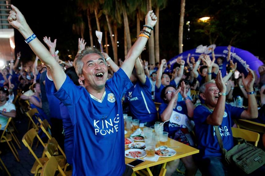 Leicester City fans celebrate after the team scored against Manchester United while watching the game on a big screen, in Bangkok, on May 1, 2016.