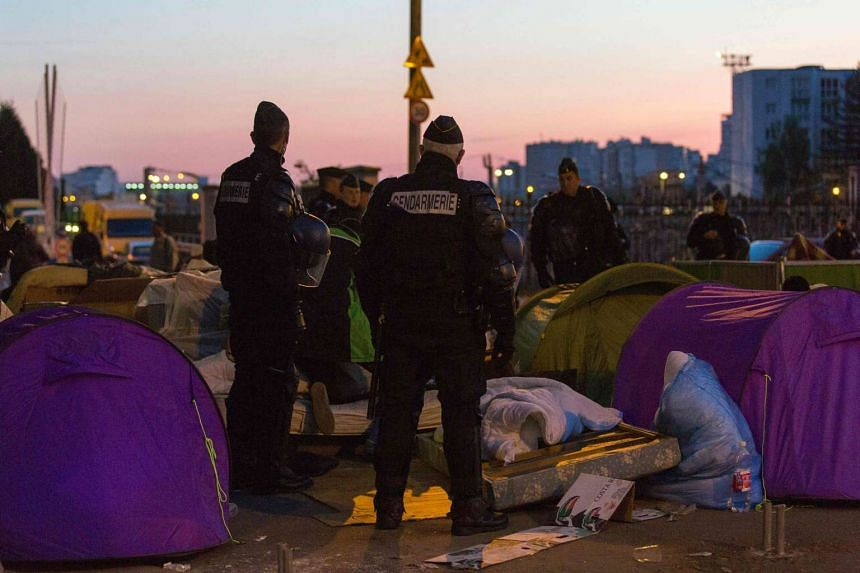 French police officers and gendarmes evacuate migrants from a makeshift camp under the Stalingrad metro station in Paris, on May 2, 2016.