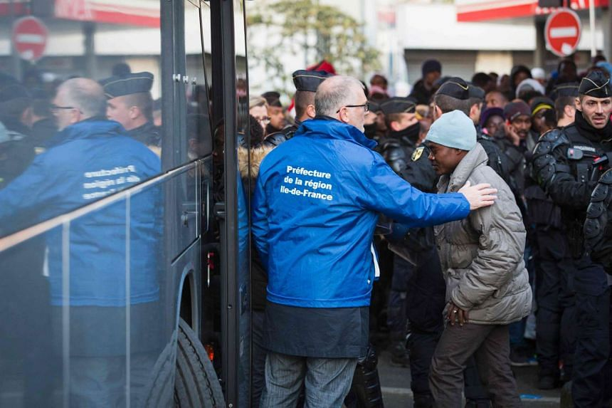 Migrants get on a bus to be transferred to reception centres from a makeshift camp under the Stalingrad metro station in Paris on May 2, 2016.