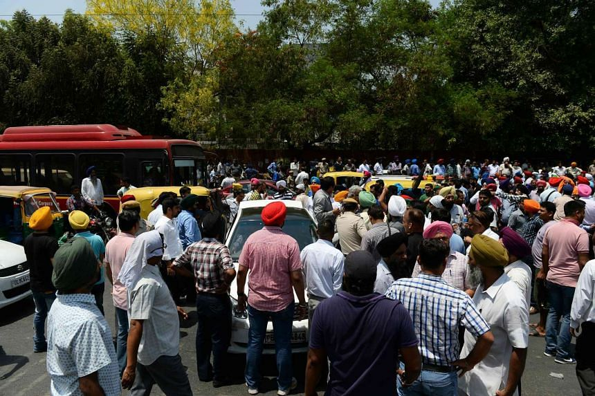 Indian taxi drivers and owners shout slogans as they block a road during a protest a court order banning diesel cabs from plying the roads in New Delhi on May 2, 2016.