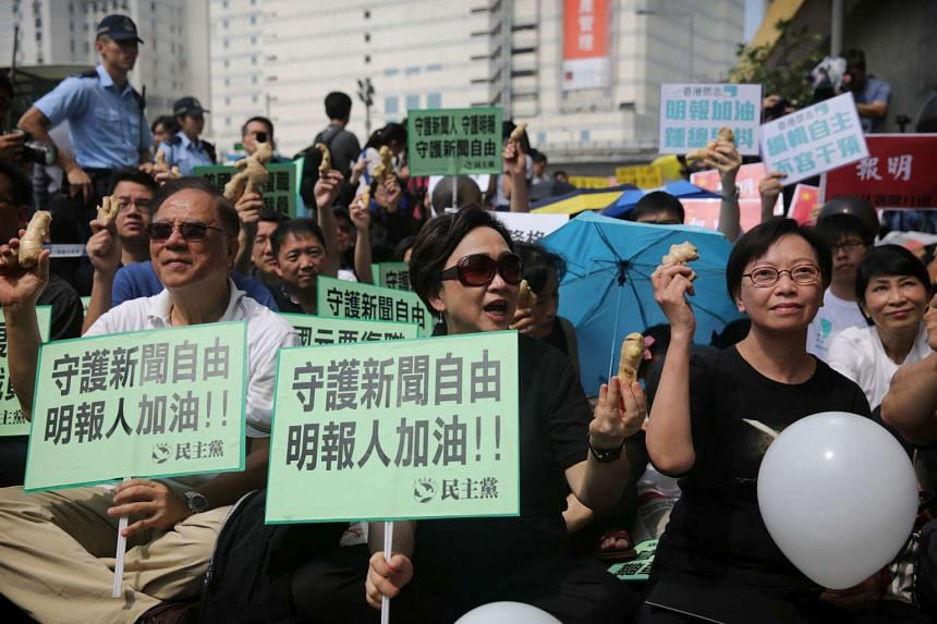 Protesters holding placards and pieces of ginger during a demonstration against the sacking of Ming Pao's executive chief editor, in Hong Kong on May 2, 2016.
