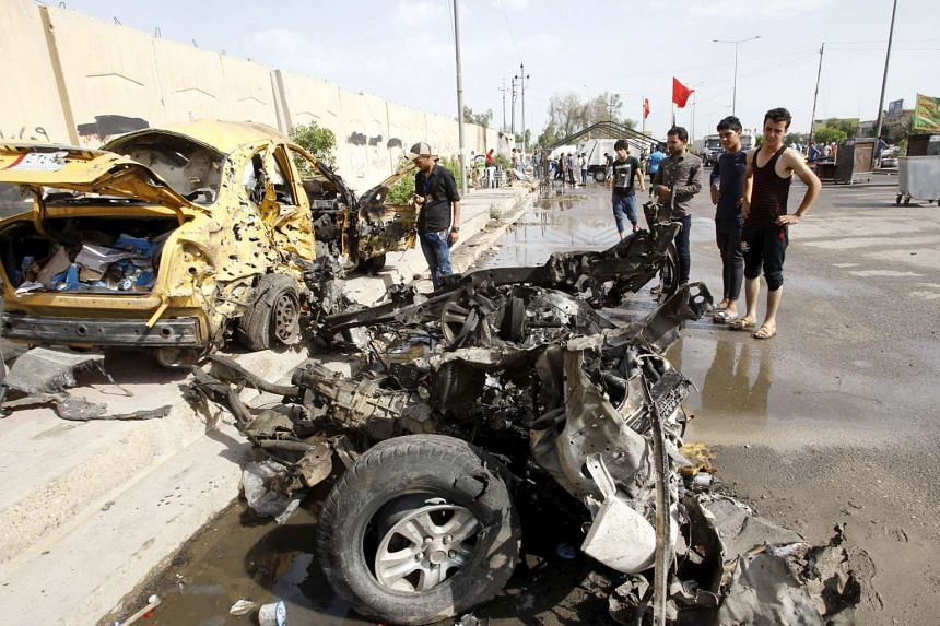 Iraqi men inspect the site of a car bomb attack in the Saydiya district of southern Baghdad, on May 2, 2016.