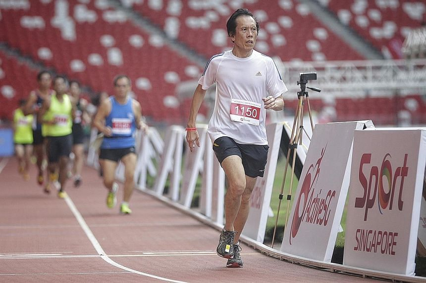 Bernard Chan (foreground) running at the National Stadium for the first time. The 64-year-old, who used to run at the old National Stadium, got the chance with other members of the public to run at the Sports Hub yesterday thanks to the ActiveSG Athl