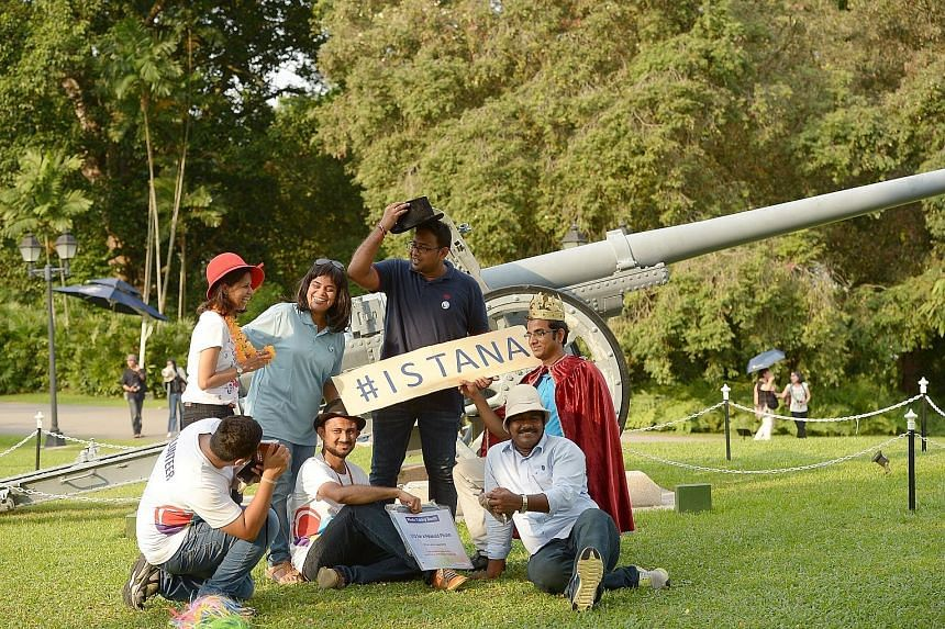 Staff from Cognizant Technology Solutions helping visitors snap a wefie in front of the 105mm Japanese cannon at the Istana during its May Day open house yesterday. The IT services firm was raising funds for the President's Challenge by running a pho