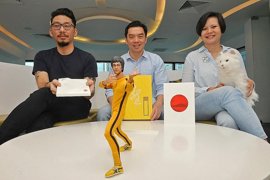 Creative directors of graphic design studio Couple Kelvin Lok (left) and Zann Wan (right) and Lien Foundation's CEO Lee Poh Wah (centre), with some of the quirky annual reports that the foundation has published over the years. Mr Lee is holding the 2