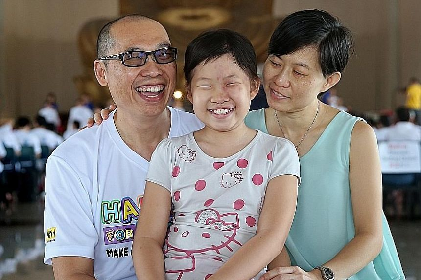 Mr Chong with his daughter Joanna and wife Pauline. Mr Chong was one of 353 participants who had their heads shaved at the Children's Cancer Foundation's Hair for Hope fund-raising event yesterday. Joanna had a tumour removed from her brain last year