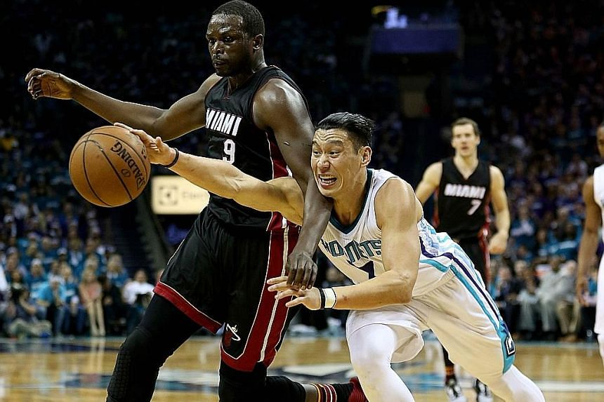 Hornets guard Jeremy Lin (right) goes after a loose ball against the Heat's Luol Deng in Game 4 of their play-off series.