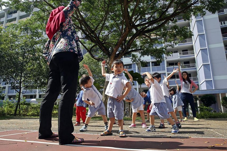 Tiny tots getting some stretching pointers from their teachers at PCF Sparkletots Preschool in Bedok North Road. Education experts say besides comparing prices when looking for a pre-school, parents may also want to observe the quality of interaction