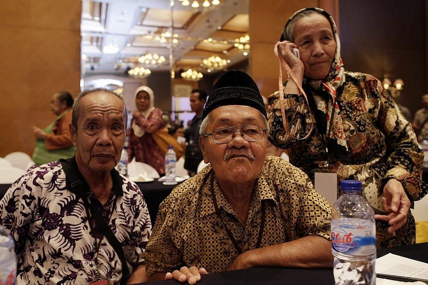 Mr Sudarno, 73, (right) who spent 14 years in prison without trial during the anti-communist purge, with a letter for the release of his father, who was detained for 12 years. He is accompanied by Mr Samin (left), 74, who was detained for 11 years. M