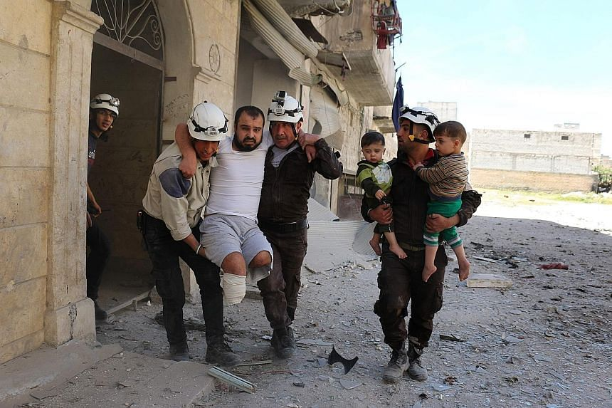 Syrian civil defence volunteers evacuating a man and children from a residential building following a reported air strike on the rebel-held eastern neighbourhood of Bab al-Nayrab in Aleppo last Friday. A new temporary truce was brokered by the US and