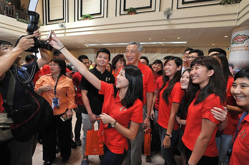 Mr Lee pausing for a wefie with participants at the May Day Rally in Downtown East yesterday. NTUC will use the $200 million to tie up with higher education institutes to help workers learn new skills in growth areas.