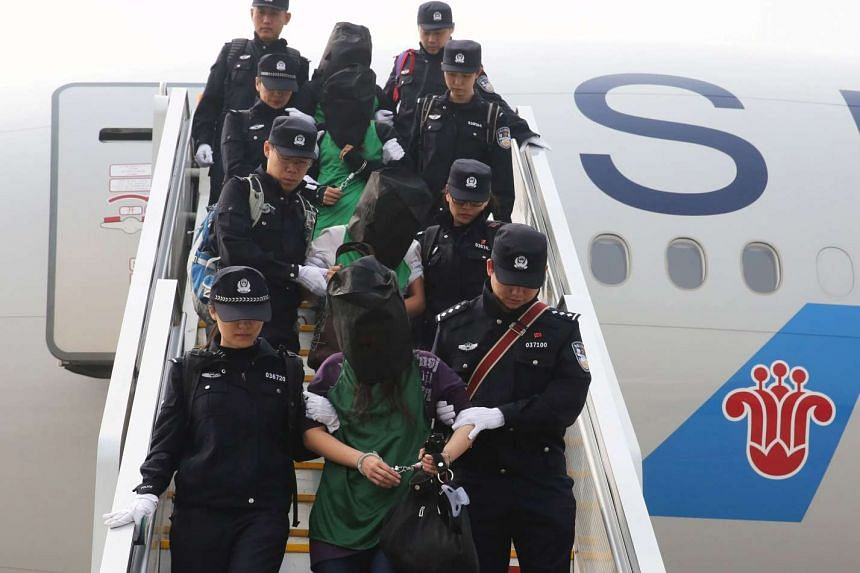 Police escort a group of people wanted for suspected fraud in China, after they were deported from Kenya, in Beijing, China, on April 13, 2016.