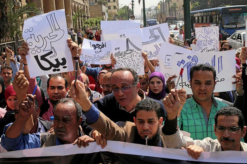 Egyptian journalists hold signs outside the Egyptian Press Syndicate following the arrest of colleagues for covering anti-government demonstrations, in Cairo, Egypt, on April 28, 2016.