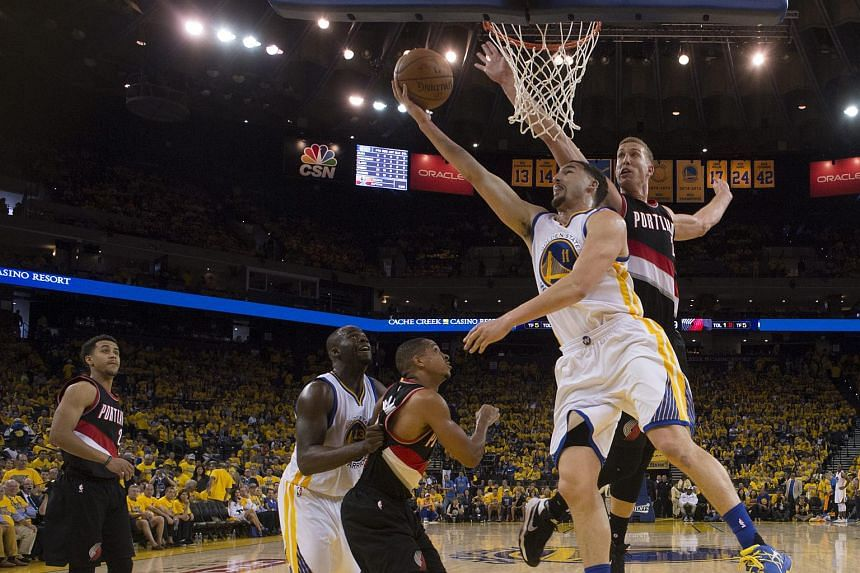 Golden State Warriors guard Klay Thompson (second from right) goes to the basket as Portland Trail Blazers center Mason Plumlee (right) defends.