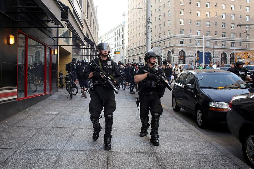 Police officers carrying non-lethal weapons during anti-capitalist protests following May Day marches in Seattle, Washington, on May 1, 2016.