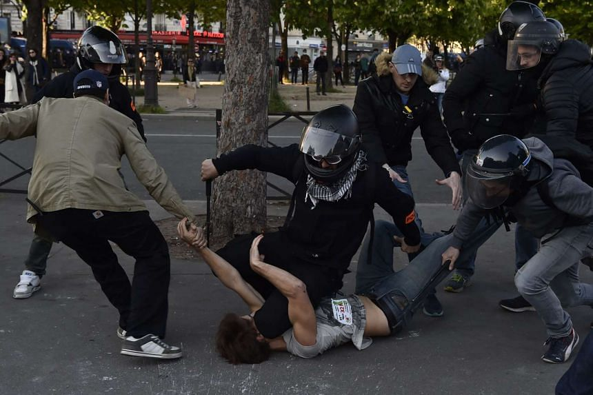 Plainclothes policemen arresting a man during clashes that broke out during the traditional May Day demonstration in Paris.